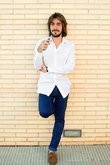 Verticale shoot van aantrekkelijke jonge man met lang haar, baard, wit shirt, blauwe broek leunend op de muur kijken glimlachen naar de camera.