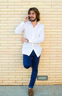 Verticale shoot van aantrekkelijke jonge man met lang haar, baard, wit shirt, blauwe broek leunend op de muur spreekt via zijn smartphone.