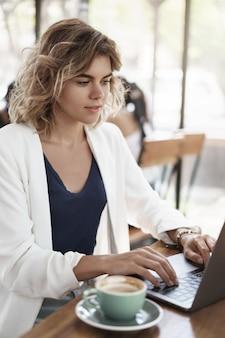 Verticale shot aantrekkelijke succesvolle zakenvrouw stijlvolle witte jas zitten café co-working ruimte koffie drinken cappucino look laptop display typen contact klant, schrijven van rapporten, project voorbereiden.