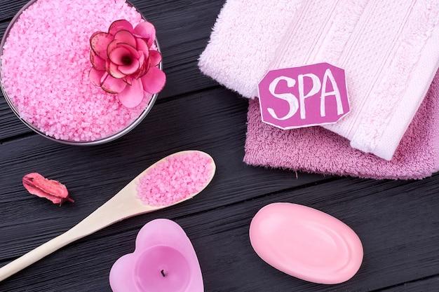 Verticale shot spa-accessoires op zwarte houten achtergrond. bovenaanzicht plat lag. roze zout en zeep.