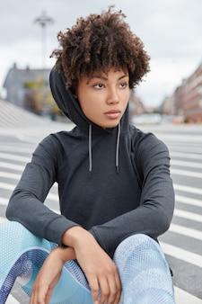 Verticale shot van aantrekkelijke doordachte afro-amerikaanse hipster draagt hoodie, zit op asfalt