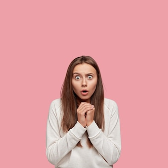Verticale shot van bang brunette blanke vrouw staart met ogen geknald zetten, houdt handen bij elkaar