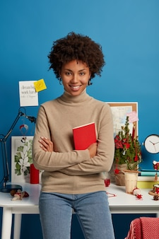 Verticale shot van blij gekrulde vrouwelijke leraar bereidt zich voor op lessen thuis, houdt rode leerboek, vormt tegen desktop