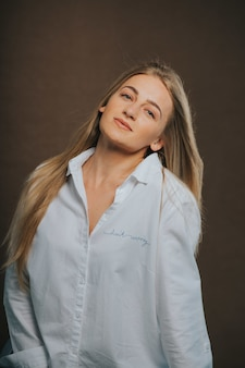 Verticale shot van een aantrekkelijke blonde vrouw in een wit overhemd poseren op een bruin oppervlak