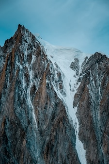 Verticale shot van een besneeuwde berg met een heldere hemel op de achtergrond