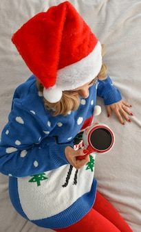 Verticale shot van een blanke blonde vrouw, gekleed in kerstkleren en koffie drinken