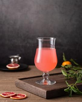 Verticale shot van een glas grapefruitsap en muntblaadjes op tafel