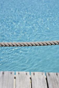Verticale shot van een grijze touw met de achtergrond van het heldere water in het zwembad