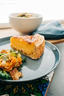 Verticale shot van een heerlijke cheesecake en wat garnituur op een bord op een tafel