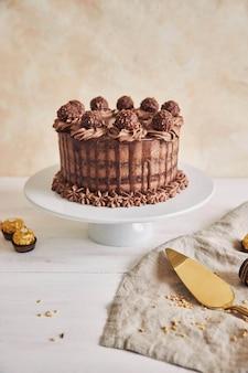 Verticale shot van een heerlijke chocoladetaart op een bord naast enkele stukjes chocolade