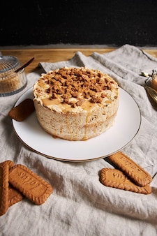 Verticale shot van een heerlijke lotus cookie-cake met karamel met koekjes op tafel