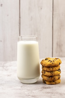 Verticale shot van een stapel chocoladeschilferkoekje naast een glas melk op een tafel
