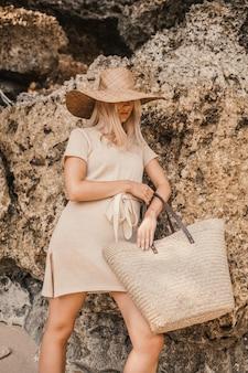 Verticale shot van een stijlvolle blonde aantrekkelijke vrouw poseren naast de kliffen overdag