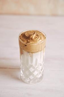 Verticale shot van een trendy heerlijke verse dalgona-koffie met melk op een witte houten tafel
