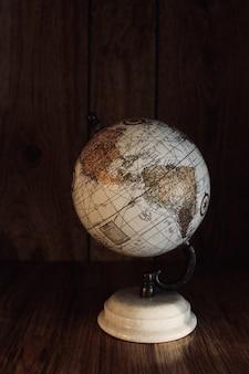 Verticale shot van een vintage globe model op een houten tafel met een houten muur op de achtergrond