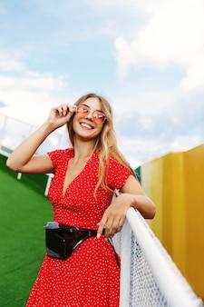 Verticale shot van een vrij blond meisje in zomerjurk en rode zonnebril, leunend op leuning in park.