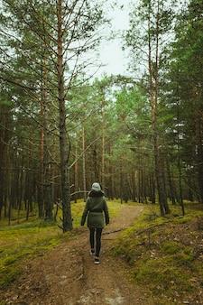 Verticale shot van een vrouw die door het bos loopt