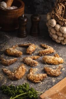 Verticale shot van gebakken kippenvleugels en wat knoflook en kruiden op een grijze ondergrond