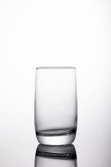 Verticale shot van glas voor water op een reflecterend oppervlak