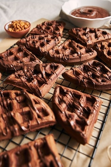 Verticale shot van heerlijke chocoladewafels op een net op de tafel in de buurt van de ingrediënten