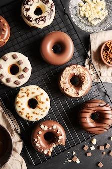 Verticale shot van heerlijke donuts bedekt met de witte en bruine chocolade glazuur op een zwarte tafel
