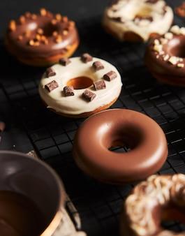 Verticale shot van heerlijke donuts bedekt met glazuur en chocoladestukjes op een zwarte tafel
