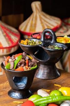 Verticale shot van heerlijke ethiopische gerechten met verse groenten op een houten tafel