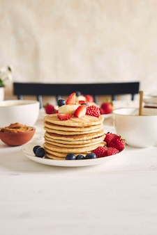 Verticale shot van heerlijke vegan pannenkoeken met aardbeien en bramen op een bord