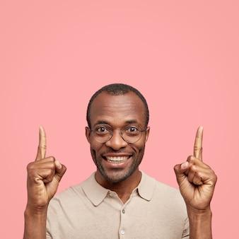 Verticale shot van lachende donkere man met een positieve uitdrukking