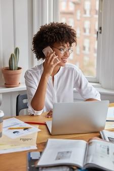 Verticale shot van mooie zwarte zakenvrouw onderzoekt grafieken op papier