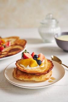 Verticale shot van pannenkoeken met fruit op de top