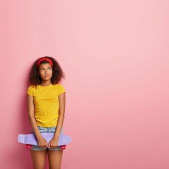 Verticale shot van slanke mooie afro-amerikaanse vrouw heeft doordachte ontevreden uitdrukking, skateboard houdt om te schaatsen, draagt rode hoofdband, geel t-shirt en denim shorts, modellen over roze muur