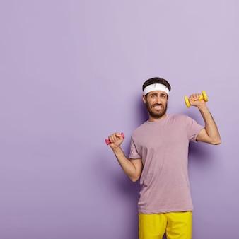Verticale shot van sportieve man gekleed in actieve slijtage, traint spieren met halters, heeft regelmatige training in de sportschool