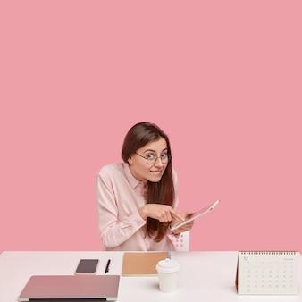 Verticale shot van vrolijke brunette jonge vrouw maakt online boeking ticket op touchpad, werkt als administratief manager