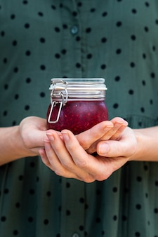 Verticale shot van vrouwelijke handen met een zelfgemaakte veganistische rauwe frambozenjam in een glazen pot