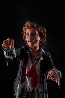 Verticale stockfoto van een kind vermomd als een zombie met bloed en glitter met opgeheven armen. halloween