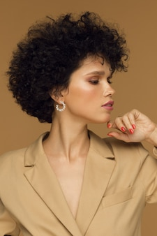 Verticale studiofoto, krullend donkerbruin meisje in een modieus jasje op een beige achtergrond. hoge kwaliteit foto