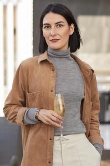 Verticale taille omhoog portret van elegante eigentijdse vrouw met champagne fluit en terwijl u geniet van feest buiten