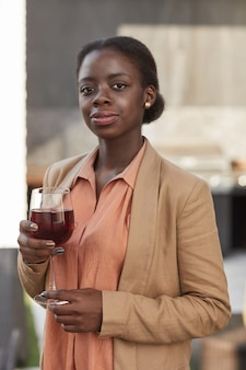 Verticale taille portret van elegante afro-amerikaanse vrouw met glas wijn en terwijl u geniet van feest buiten