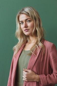 Verticale taille portret van elegante blonde vrouw stoffige roze jas dragen en terwijl poseren tegen een groene achtergrond in de studio