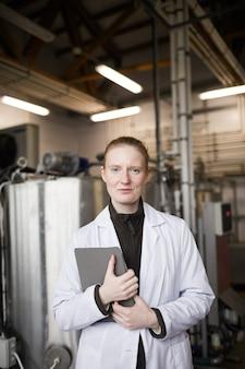 Verticale taille portret van jonge vrouw dragen laboratoriumjas poseren tegen machines tijdens het werken in zuivelfabriek