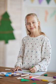 Verticale taille portret van lachende blonde meisje camera kijken terwijl staande door tafel te maken en te genieten van kunstles op school