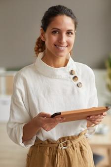 Verticale taille portret van lachende succesvolle zakenvrouw camera kijken en digitale tablet te houden tijdens het werken vanuit huis of op kantoor