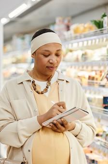 Verticale taille portret van zwangere afro-amerikaanse vrouw die boodschappen doet in de supermarkt en een lijst vasthoudt