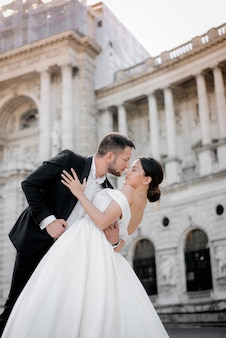 Verticale trouwfoto van bruid en bruidegom een moment voor een kus voor historisch gebouw