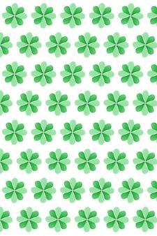 Verticale vakantie van groene natuurlijke klaverplant met vier bloemblaadjes handgemaakt van gekleurd papier op een witte muur. gelukkig st.patrick's day-concept.
