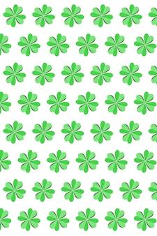 Verticale vakantiesamenstelling van handwerkpapier groene klaverblaadjes op een wit met kopie ruimte. gelukkig st.patrick's day-concept.