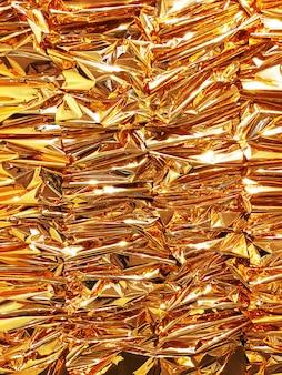 Verticale verfrommelde gouden foliedocument textuurachtergrond.