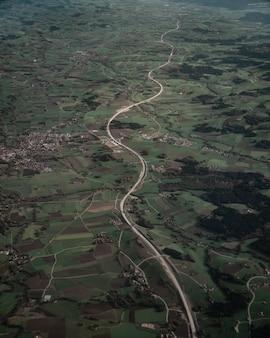 Verticale vogelvlucht van een eindeloze weg en groene velden