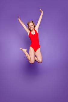 Verticale volledige grootte van mooi grappig meisje duiken uit bungee geïsoleerd paars violet